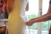 Wedding preparation, wedding gown being tied up