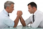 picture of offensive  - businessmen arm wrestling - JPG