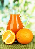 Orange juice in pitcher on table on bright background