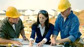 image of erection  - Contractors look at and discuss plans with an architect - JPG