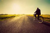 stock photo of retired  - Old man riding a bike on asphalt road towards the sunny sunset sky - JPG