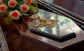 stock photo of casket  - Dark wooden coffin with Jesus crucifix and roses - JPG