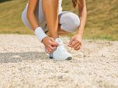 stock photo of snickers  - Young woman is tying laces on her snickers - JPG