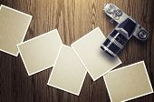 Blank card and vintage camera on wood background.