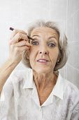 Portrait of senior woman applying eyeliner in bathroom