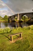 stock photo of william wallace  - The ancient medieval bridge at Stirling captured in the soft light of early morning with a rainbow in the background.