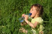 Girl Sits In Grass And Drinks Water From Plastic Bottle
