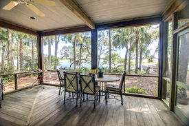 stock photo of screen-porch  - rustic screen porch with forest and waterfront view - JPG