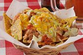 picture of nachos  - A basket of been and cheese nachos on black bean corn chips - JPG