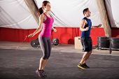 stock photo of jump rope  - Young man and woman jumping ropes as part of their workout in a gym - JPG