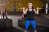 image of squatting  - Three people working out in a crossfit gym using weights and tires - JPG
