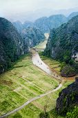 stock photo of early morning  - Tourist boats floating on the river among rice fields and limestone rocks in the early morning at Tam Coc near Ninh Binh Vietnam - JPG