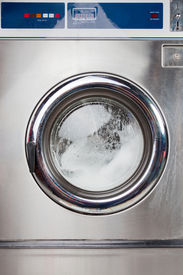 pic of laundromat  - Closeup of automatic washing machine in laundromat - JPG