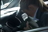 stock photo of nervous breakdown  - Depressed young woman sitting in a car leaning to steering wheel - JPG