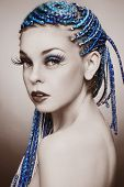 stock photo of dreads  - Sepia coloured portrait of young beautiful girl with blue braids and huge fancy fake eyelashes - JPG