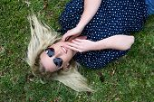 stock photo of splayed  - Lovely young lady relaxing on the grass and wearing heart shaped sunglasses and hair splayed - JPG