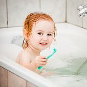 stock photo of 15 year old  - cute two year old baby bathes in a bath with foam closeup - JPG