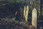 stock photo of grieving  - A grieving woman dressed in black is sitting by a grave - JPG