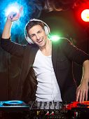 pic of mixer  - Portrait of a young smiling dj with mixer on foggy background - JPG
