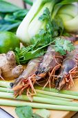 picture of tiger prawn  - Ingredients for Thai tom yam soup laid out on a kitchen counter with tiger prawns mushrooms ginger lemongrass limes celery parsley and spices - JPG