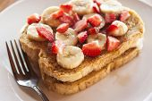 foto of french toast  - Two slices of French toast with sliced bananas and strawberries on top - JPG
