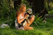 image of stray dog  - A young beautiful woman with blonde hair is holding lovingly a stray dog in her arms in a backyard garden with green grass - JPG