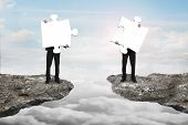stock photo of comrades  - Businessmen holding two white jigsaw puzzles to connect on the cliff with cloudscape sunlight background - JPG