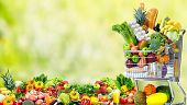 picture of grocery cart  - Shopping cart with vegetables over green background - JPG