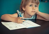picture of homework  - Five year old boy dreaming while doing his math homework  - JPG