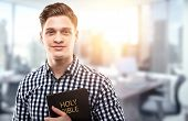 stock photo of holy-bible  - Young man holding a Bible in a modern office  - JPG