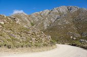 foto of dirt road  - Dirt road leading over a high mountain pass in daytime - JPG