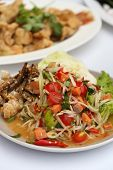 pic of green papaya salad  - papaya spicy salad with salmon on white table in restaurant - JPG