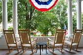 pic of usa flag  - Four vacant wooden rocking chairs lined up on a patio overlooking a lush garden below a draped American flag symbolising 4th July commemorating Independence Day - JPG