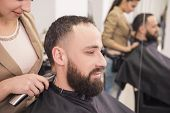 pic of hair cutting  - Hairdresser cutting hair with hair clipper on back of the head in hairdressing salon