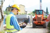 stock photo of worker  - construction worker in safety protective work wear with laptop computer  at construction site in front of loader machinery - JPG