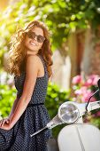 picture of scooter  - Young beautiful italian woman sitting on a vintage scooter - JPG