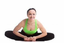 stock photo of ashtanga vinyasa yoga  - Cheerful smiling sporty girl doing yoga practice sitting in bound angle posture baddha konasana cobbler pose - JPG