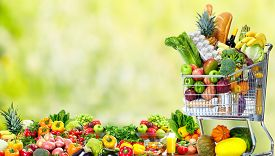 pic of grocery cart  - Shopping cart with vegetables over green background - JPG