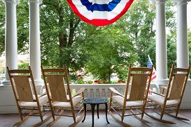 stock photo of four  - Four vacant wooden rocking chairs lined up on a patio overlooking a lush garden below a draped American flag symbolising 4th July commemorating Independence Day - JPG