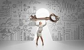 foto of keyhole  - Young businesswoman and keyhole at background lifting big key above head - JPG