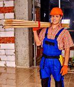 foto of millwright  - Happy man in builder uniform carry wooden boards indoor - JPG