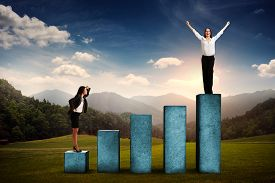 picture of step-up  - businesswoman standing at the lower step of diagram and looking up at the winner over beautiful forest landscape - JPG