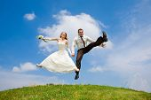 stock photo of wedding couple  - Groom and bride jumping against backdrop a sky and trees - JPG