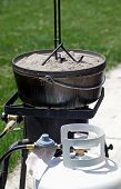 image of dutch oven  - Dutch oven on a propane cooker with propane tank - JPG