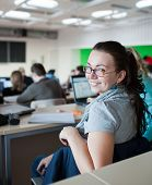 foto of students classroom  - young pretty female college student sitting in a classroom full of students during class - JPG