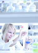 stock photo of retort  - Closeup of a female researcher holding a test tube and a retort and carrying out experiments in a laboratory - JPG