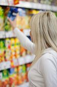 pic of fruit-juice  - Beautiful young blonde woman shopping for fruit juices - JPG