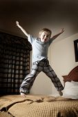 stock photo of disobedient  - Young boy jumping on the bed - JPG