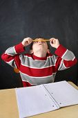 stock photo of fidget  - Bored student balancing a pencil on his nose - JPG