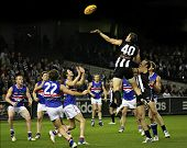 Collingwood's Chris Bryan taps the ball to Scott Burns for a goal agains the Western Bulldogs, June